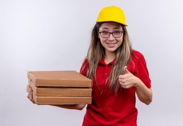 赤いポロシャツと黄色い帽子の臆病な若い配達の女の子は、親指を上げて笑っているピザの箱のスタックを保持しています 無料写真
