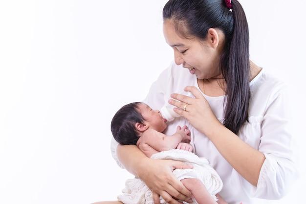 Крошечный очаровательный новорожденный ребенок пьет молоко из бутылочки и смотрит на свою красивую мать Premium Фотографии