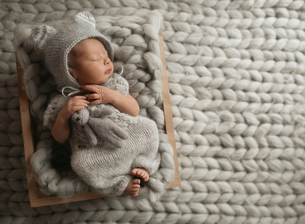 Tiny baby in grey clothes sleeps on woolen blanket Free Photo