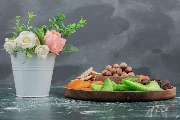 大理石の壁にドライフルーツの木製プレートと小さな花束。 無料写真