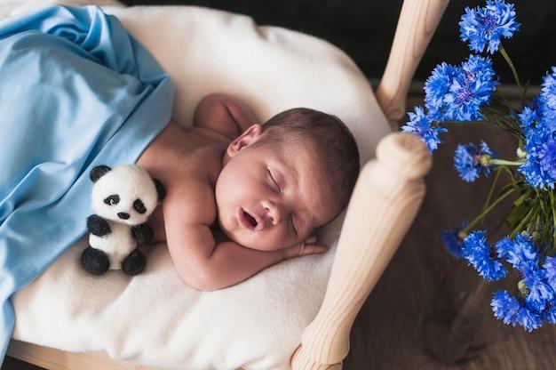 Tiny child under blue blanket Free Photo