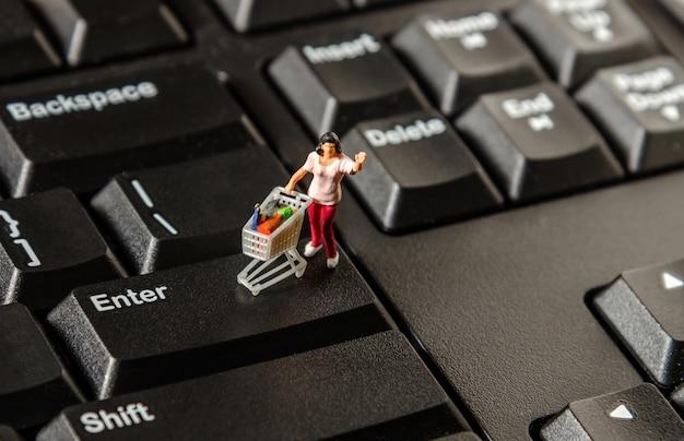 Tiny miniature figurine woman with shopping cart Premium Photo