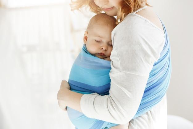 Крошечный новорожденный ребенок закрывает глаза и, хорошо выспавшись, в слинге чувствует защиту от своей красивой молодой мамы. семья, концепция образа жизни. Бесплатные Фотографии