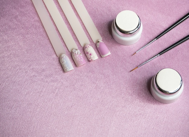 Tips and paint for drawing on nails on a pink table. creative manicure concept. Premium Photo