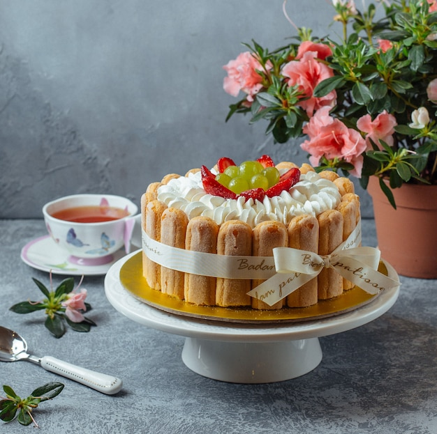 Tiramisu cake with lady finger cookies and berries with a cup of tea and flowers. Free Photo
