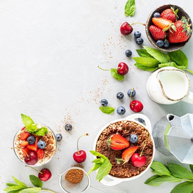 ティラミスイタリアのデザートと食材。コーヒー、ココア、イチゴ、白い背景の上のミント。コピースペースの上面図 Premium写真
