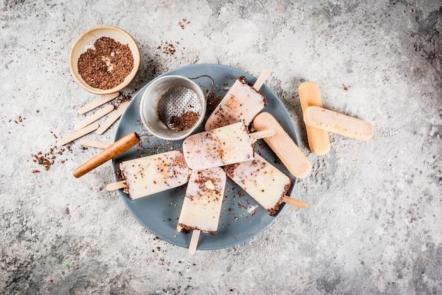 Tiramisu popsicles ice cream. gelato pops with italian savoiardi cookies, mascarpone, milk chocolate Premium Photo