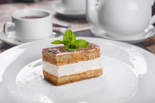 Tiramisu with mint on a white plate Premium Photo