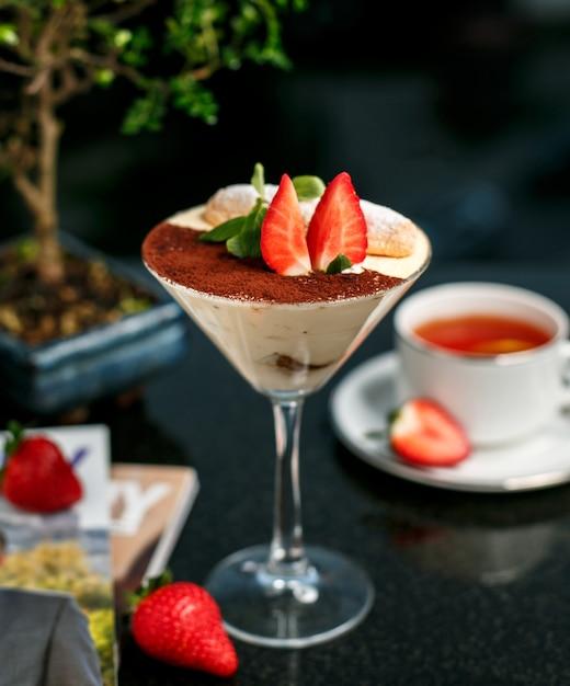 Tiramisu with strawberry on the table Free Photo