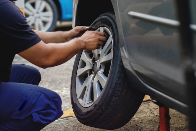 Tire replacement concept. mechanic working his job with wheel in garage. car maintenance and services Premium Photo