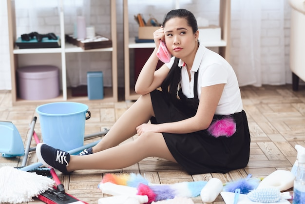 Tired asian chambermaid lady sitting on floor Premium Photo
