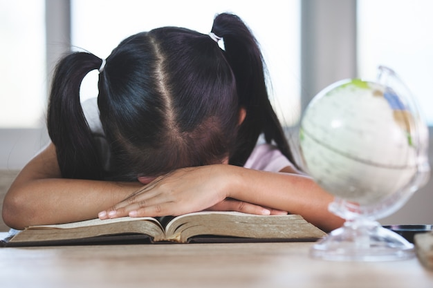 Tired asian little child girl sleeping over the opened book in the classroom Premium Photo