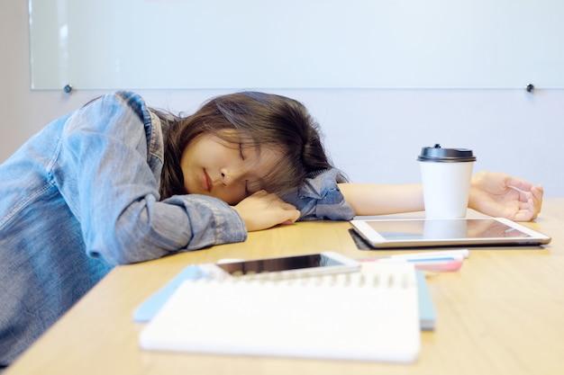 オフィスの机で寝ている疲れているアジア女性。 Premium写真