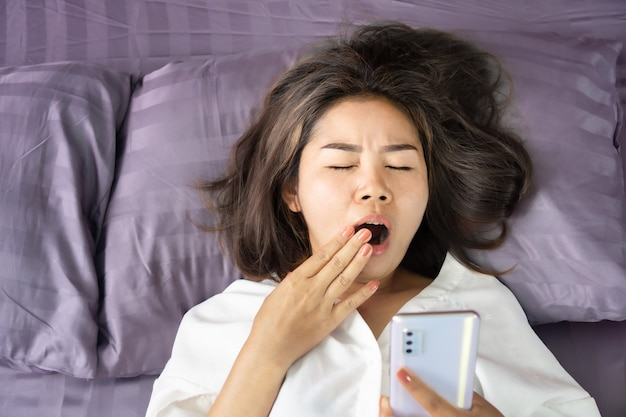 Tired asian woman yawning in bed hand holding smart phone Premium Photo