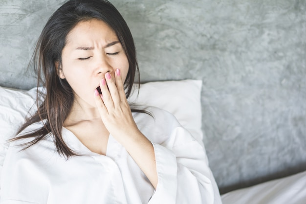 Tired asian woman yawning in bed Premium Photo