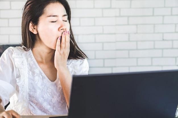 Tired asian woman yawning at workplace Premium Photo