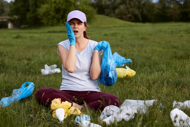 Tired astonished female picking up litter on green meadow Free Photo