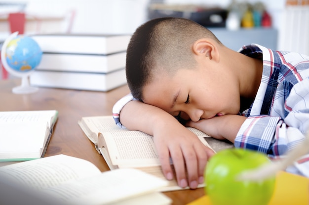 Tired and bored boy sleeping among the books. Premium Photo