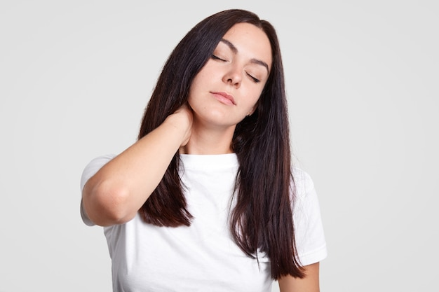 Tired brunette female feels pain in neck as has sedentary lifestyle, needs physical activity, closes eyes, wants sleep Free Photo