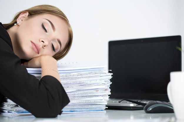 Tired business woman slleeping on heap of papers at her working place. overwork, working overtime and stress at work concept. Premium Photo