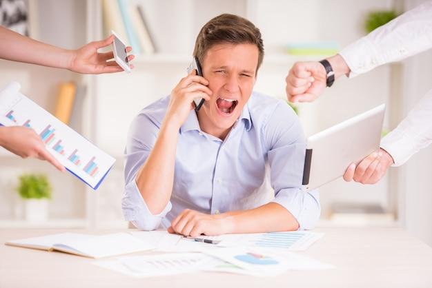Утомленный бизнесмен в своем кабинете кричит. Premium Фотографии
