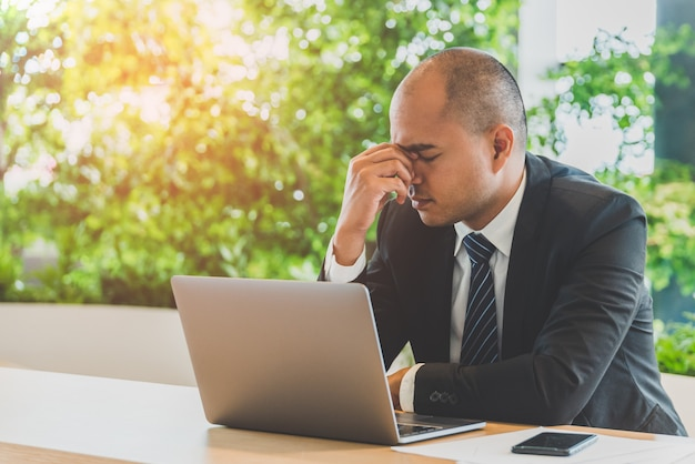Tired businessman rubbing his eyes. office syndrome concept. Premium Photo