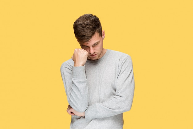 Tired businessman or the serious young man over yellow studio with headache emotions Free Photo