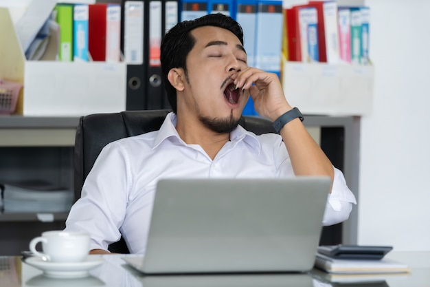 Tired businessman using laptop and yawning Premium Photo