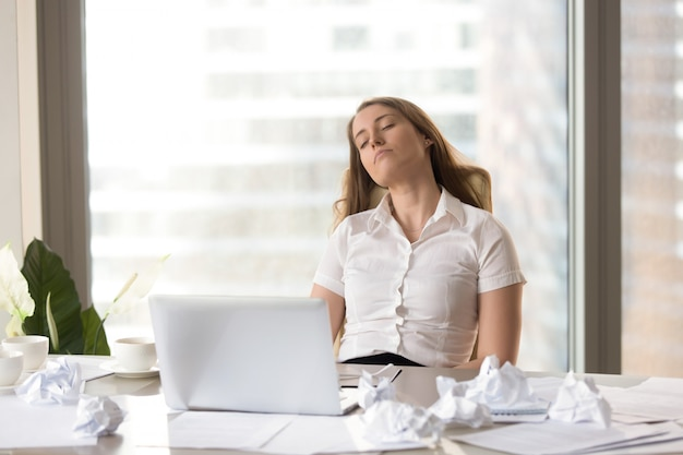 Tired businesswoman sleeping in chair at the desk Free Photo