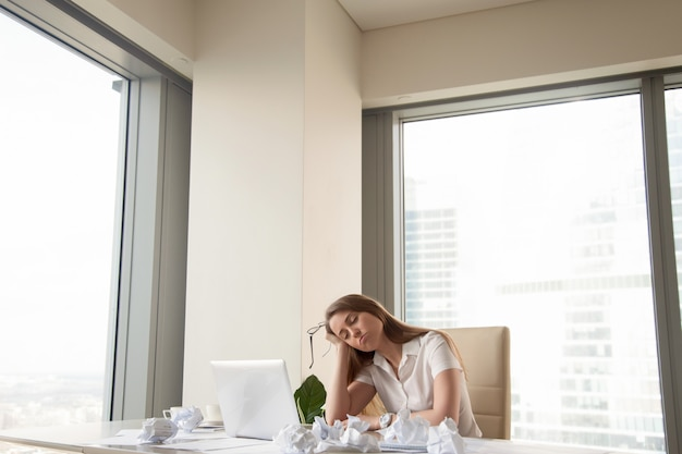 Tired businesswoman unproductive to finish urgent work, too much paperwork Free Photo