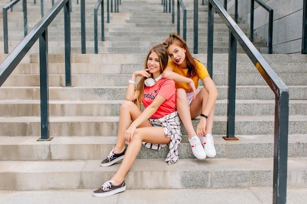 親友と石段でリラックスしてトレンディな白いスニーカーで疲れているが満足しているブルネットの女の子 無料写真