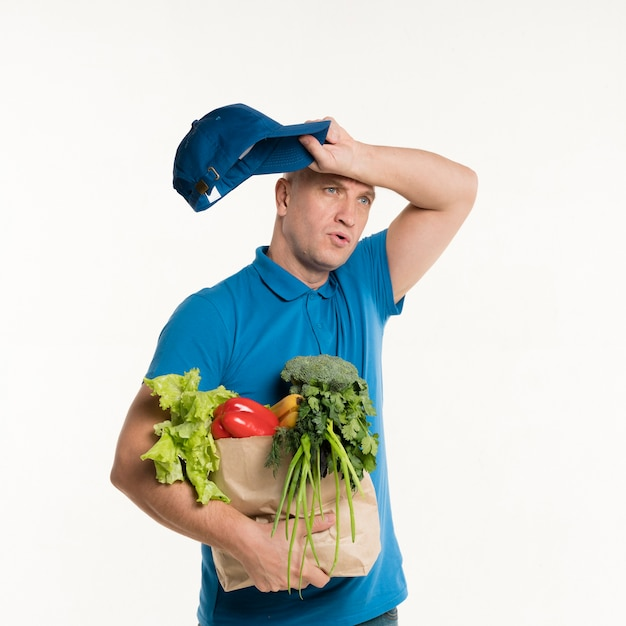 Tired delivery man posing with grocery bag Free Photo