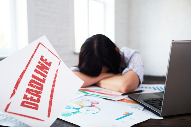 Tired disturbed female worker with headache.stressed woman in office holding head in hands and thinking about deadline Premium Photo