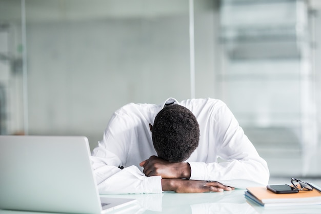 Tired employee in formal wear fall asleep after long working hours in office Free Photo