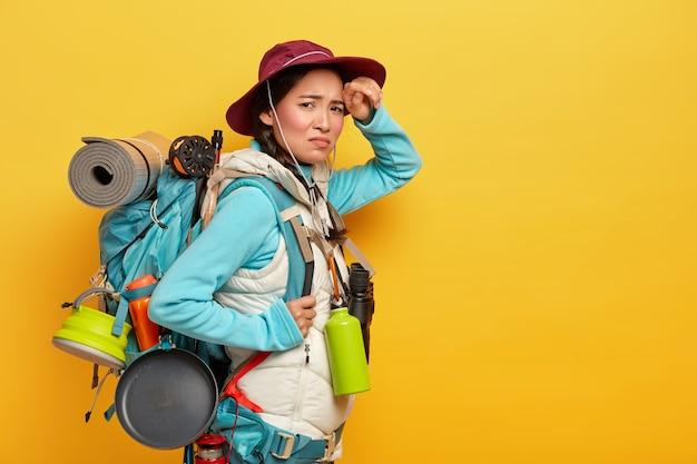 Turista femminile stanco esausto cammina per lunghe distanze a piedi, guarda con insoddisfazione alla telecamera, si erge di lato contro il muro giallo, trasporta lo zaino con cose personali Foto Gratuite