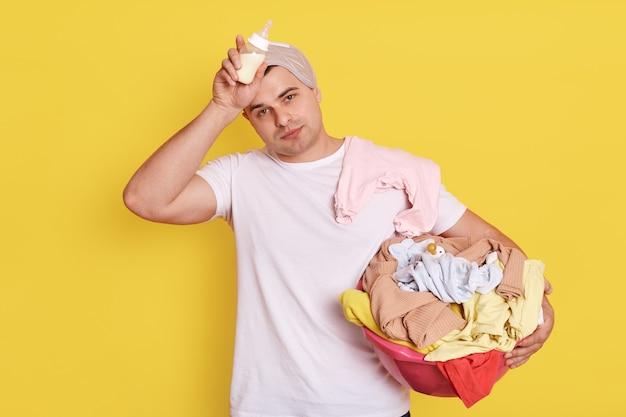 Усталый измученный муж, который стоит с детскими предметами в изоляции над желтой стеной, отец держит в руках бутылочку для кормления, держит руку на ее лбу. Premium Фотографии