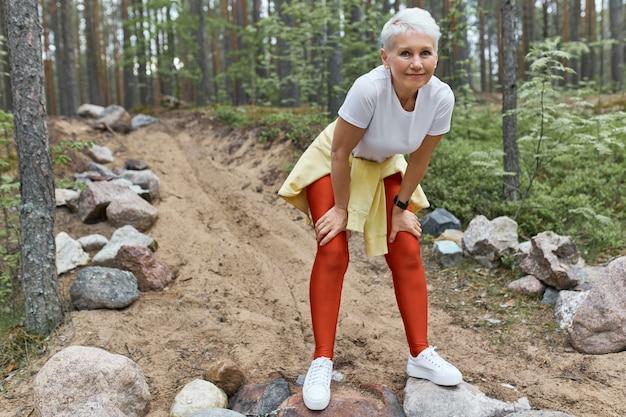 Усталая истощенная женщина средних лет в спортивной одежде и кроссовках отдыхает после интенсивной кардиотренировки Бесплатные Фотографии