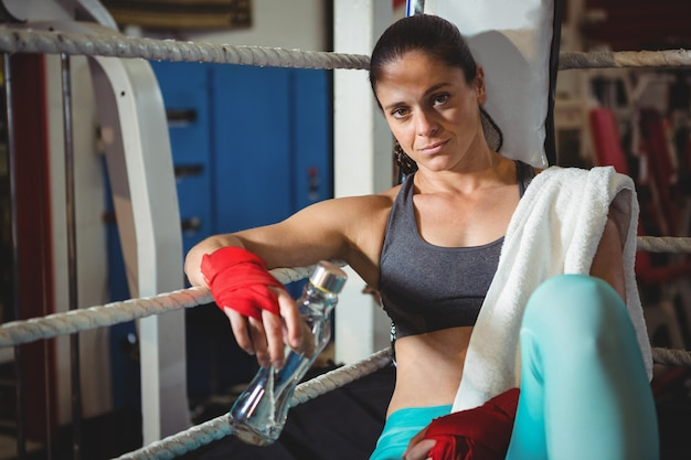 Tired female boxer sitting in the ring Free Photo