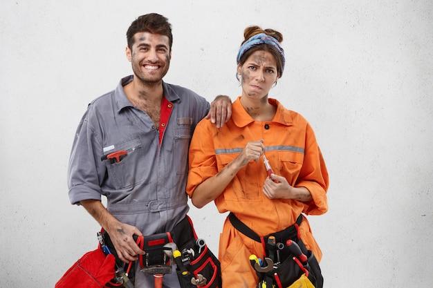オレンジ色の制服を着た女性の大工に疲れて、幸せな表情でドライバーと男性の同僚を保持しています。 無料写真