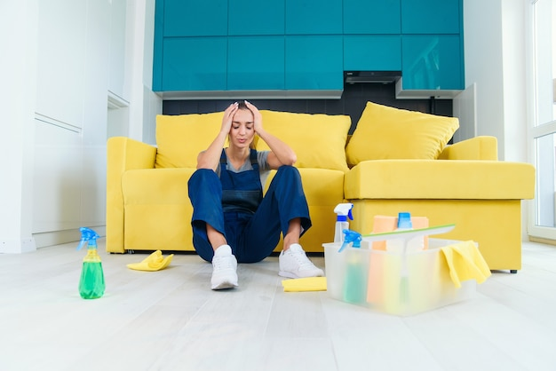 Tired female worker of the cleaning service sitting near the couch and feeling sad after washing floor on cuisine. Premium Photo