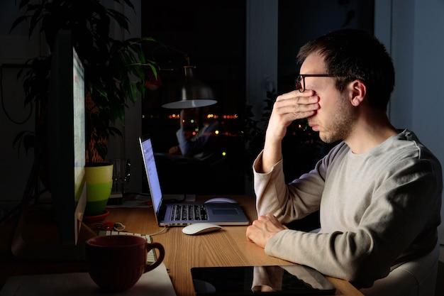Усталый фрилансер, протирая глаза, сидя за настольным пк / ноутбуком поздно ночью, в период самоизоляции и удаленной работы дома, засыпает от усталости. Premium Фотографии