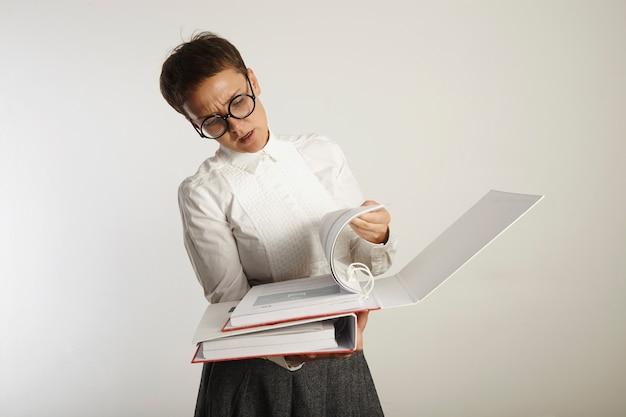 Giovane insegnante donna stanca e accigliata in abito conservatore e occhiali rotondi neri che gira le pagine in uno spesso raccoglitore su bianco Foto Gratuite