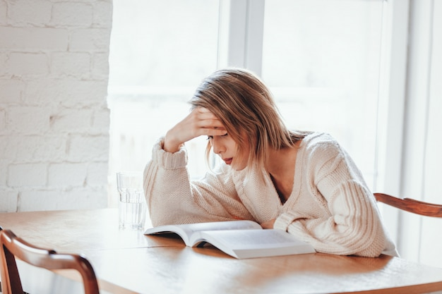 Tired girl in white sweater with book at kitchen Premium Photo