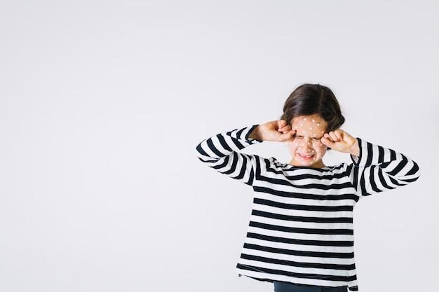 Tired girl with rash rubbing eyes Free Photo