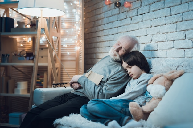 Tired grandpa and granson sleeping after hard day Premium Photo
