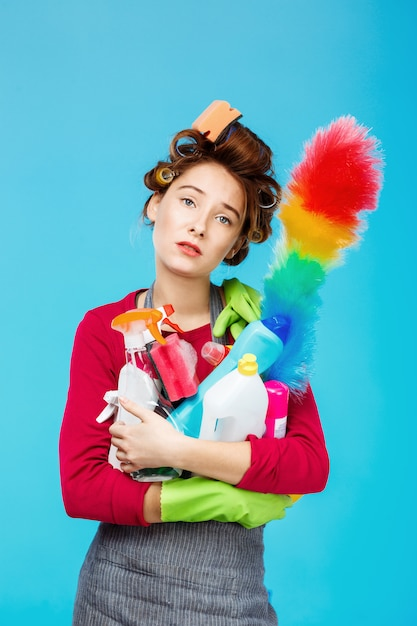Tired housewife in pink outfit holds duster and cleaning tools Free Photo