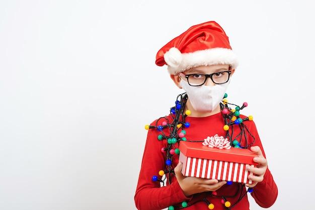 격리 기간 동안 크리스마스 선물로 피곤한 작은 산타. 프리미엄 사진