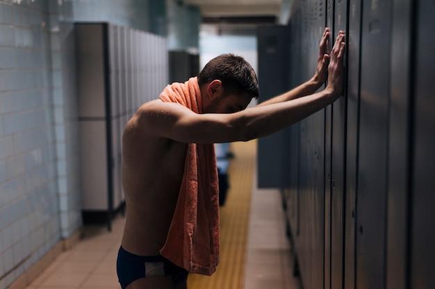 Tired male swimmer in locker room Free Photo
