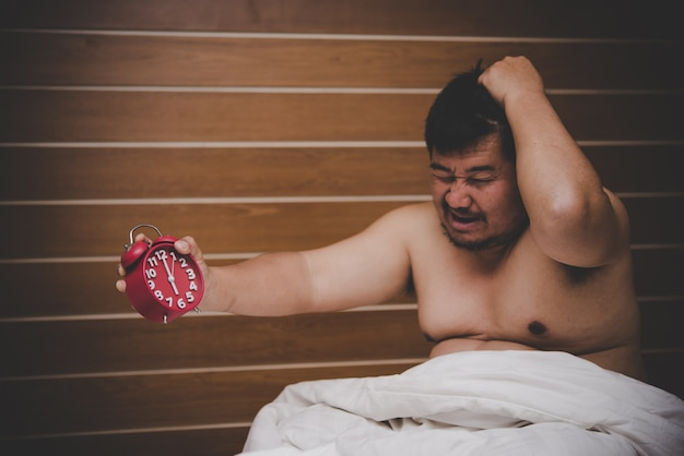 Tired man get angry when alarm clock wake him up in the morning. Premium Photo