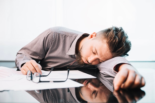 Tired man sleeping in office Free Photo